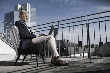 Grey-haired businessman sitting on balcony using laptop