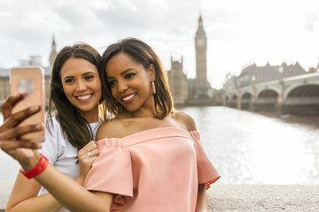 UK, London, two beautiful women taking a selfie near Westminster Bridge