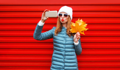 Fashion autumn pretty woman takes a picture self portrait on a smartphone with maple leaves on red background