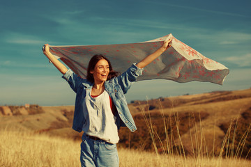 Young woman holding a scarf in the wind on a mountain