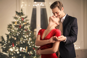 Sweet couple kissing in front of a Christmas tree