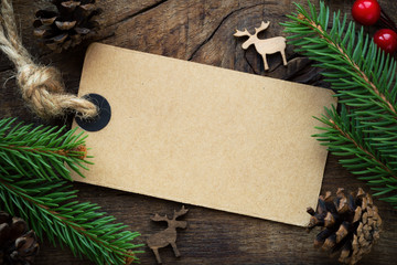 Kraft paper empty tag with Christmas ornaments on dark rustic wooden background. Overhead view