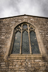Church window with authentic gothic style and lights inside