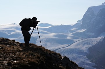 Silhouette picture of a photographer standing on the mountain and taking a photo. Snow mountain background