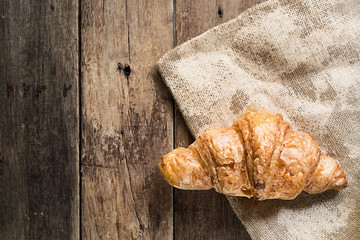 Illustration of fresh butter croissant on gunny sack cloth on wooden table with copy space, top view, watercolor painting effect