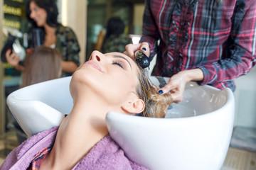 Working day inside the hair salon, hairdresser washing hair.