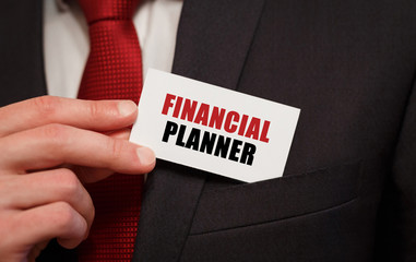 Businessman putting a card with text FINANCIAL PLANNER in the pocket