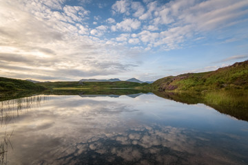 Sharp reflection of the warm colored clouds in the water of tarn Beacon Lake District mountain background