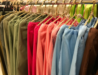 Colorful hanging woman linen pants on rack