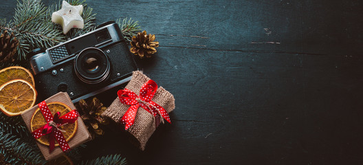 Camera Christmas wooden background. New Year's holiday. Christmas motive. On a wooden surface. Top view. Free space for your text.