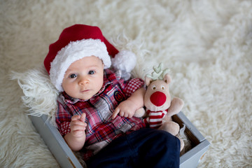 Christmas portrait of cute little newborn baby boy, dressed in christmas clothes