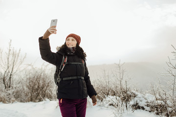 Smiling woman dressed warm taking a selfie in a snowy country.