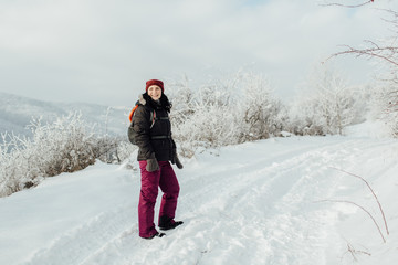 Smiling woman dressed warm enjoying a walk in snowy country.