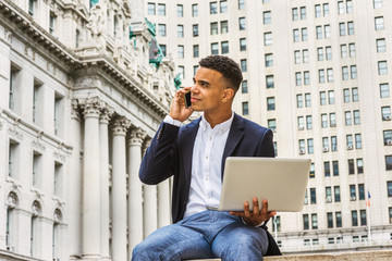 Modern life. African American college student studying in New York, sitting by vintage office building on street, reading, working on laptop computer, talking on cell phone. Instagram filtered effect