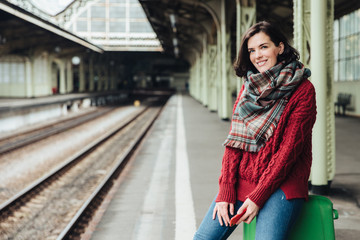 Beautiful woman wears knitted sweater and scarf, sits on suitcase near platform, holds smart phone in hands, waits for train, going to travel in other country, Female traveller with happy expression