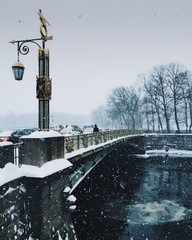 Winter landscape, river and bridge in big city. Frosen river water. Snowfall over city background. Picture of charming winter time. View of beautiful nature