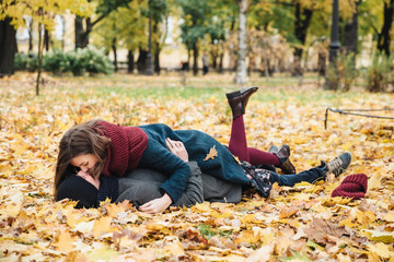Boyfriend and girlfriend have romantic kiss as lie on yellow leaves in park, spend sunny autumn weekends together, have good mood. Couple in love enjoy togetherness outdoors. Season and people