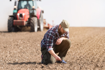Young farmer examing dirt while tractor is plowing field