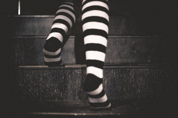 women's socks in black and white stripes. The girl climbs the stairs