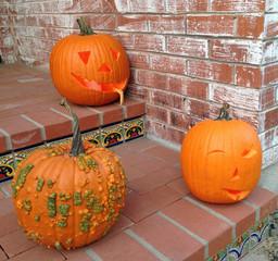 Drei Halloween-Kürbisse mit geschnitzten Gesichtern auf Stufen vor Backstein-Hauswand