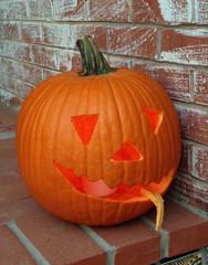 Halloween-Kürbis mit geschnitztem Gesicht auf einer Stufe vor Backstein-Hauswand