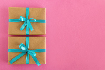 Two gift boxes wrapped of craft paper and blue ribbon on the pink background, top view.