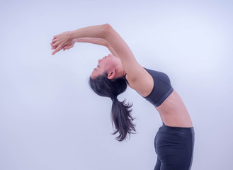 Beautiful young Asian doing yoga exercise. Healthy young girl practicing yoga.  Healthy lifestyle and good wellness concepts