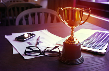 Trophy on work table, win concept