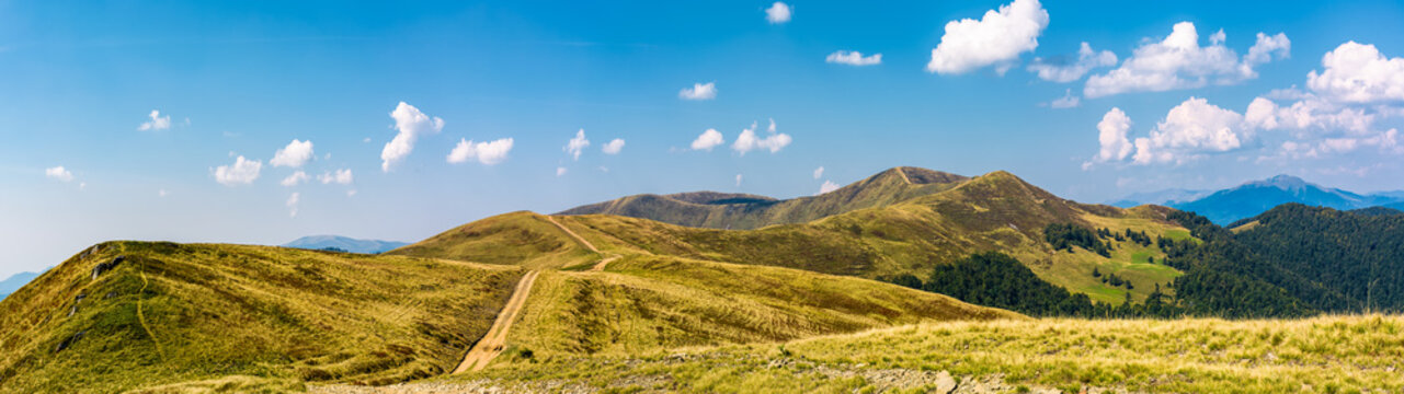 footpath through rolling hills of mountain ridge. gorgeous panorama of early autumn landscape with fine weather and blue sky with some clouds. hiking direction concept