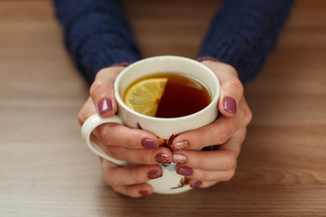 women's  hands holding a cup on a wooden background cup of hot tea with lemon morning tea fragrant tea with lemon and chants on a wooden background two hands with a white cup on the table