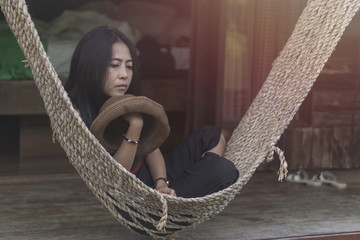 Asian girl on wood cradle in the resort., kanchanaburi thailand., Asian woman is sleeping on the cradle., relaxing concept. image vintage style.