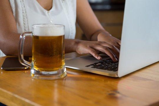 Woman using laptop at bar