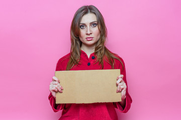 portrait serious cute young brunette girl with long haire in red pajamas with a cardboard sign in hands. Template.