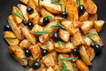 Delicious baked potatoes with rosemary and olives on black background