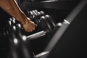 Dumbbell. Close-up man grabs a heavy dumbbell in the gym with his hand. Concept lifting, fitness.