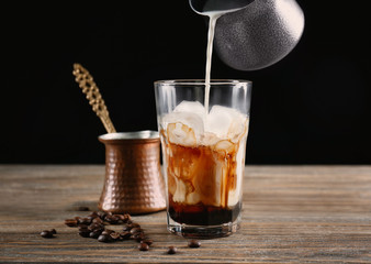 Pouring milk into glass with iced coffee on black background