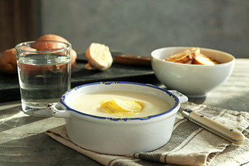 Tureen with potato cream soup on table