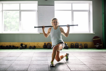 beautiful young woman doing sit-up exercises with a weight stick on the buttocks in the gym