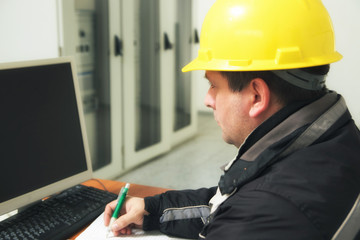 Technician take notes in the power plant control center