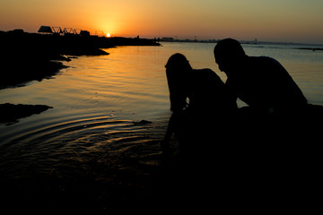 Sunset love story in the sea. Young couple make the sign of hands hearts in the air before sunrise. Silhouette at sunset. Sweethearts. Love Story. Young couple in love.