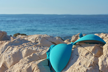 top bikini part lying on the rock by the sea