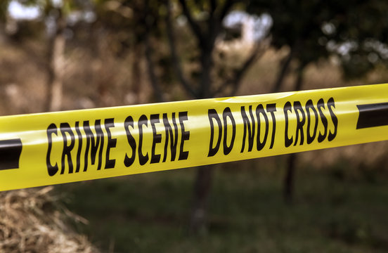Crime scene tape closeup, police tape Do Not Cross outdoors