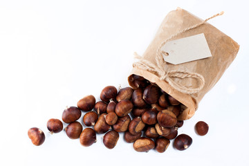edible chestnuts - a bag of fresh, raw chestnuts sprinkled on a white background