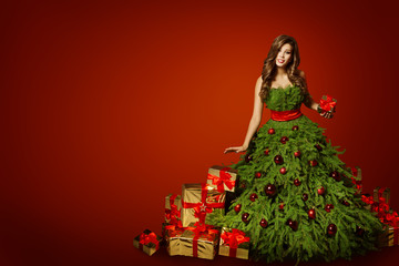 Woman Christmas Tree Dress with Present Gift, Xmas Fashion Gown over Red New Year Background