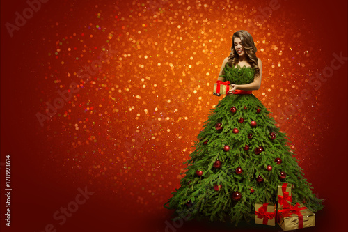 woman in christmas tree dress holding present gift fashion girl over new year red background