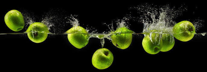 Green apple falling in water on black background Wall mural