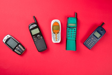 Old mobile phones on red background