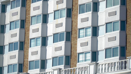 Establishing shot day time exterior close up hotel room window facade. Generic architecture design of bay windows and air conditioning units of five star vacation resort location
