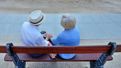 Pair of older people sitting on bench.