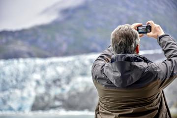 a senior in Alaska on a cruise ship admiring glacier taking photo